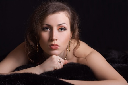 beautiful stylish woman in jewelry lies on black fur