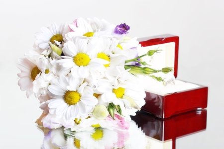 bridal bouquet of daisies and a box with a ring