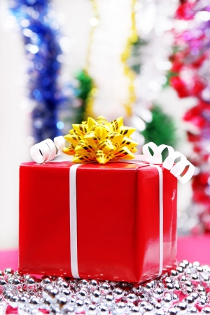 Christmas gift box red with a yellow bow on a bright background photo