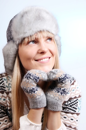 beautiful young smiling woman in a knitted sweater and fur hat Stock Photo - 11392153