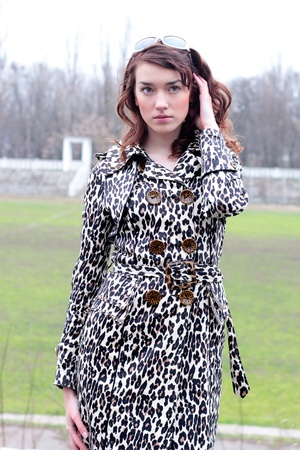 beautiful girl in a stylish leopard coat outdoor Stock Photo