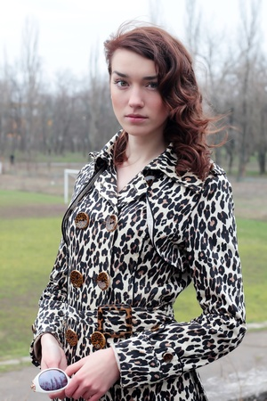 wind blown hair: beautiful girl in a stylish leopard coat on the street Stock Photo