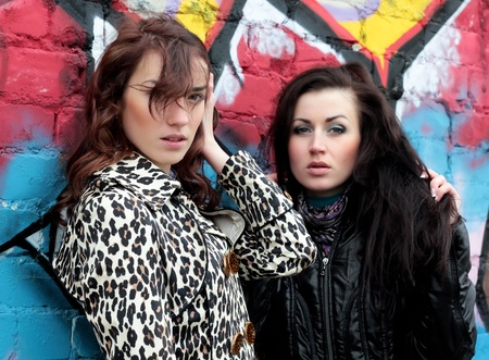 wind blown hair: two beautiful fashionable girls outdoor Stock Photo