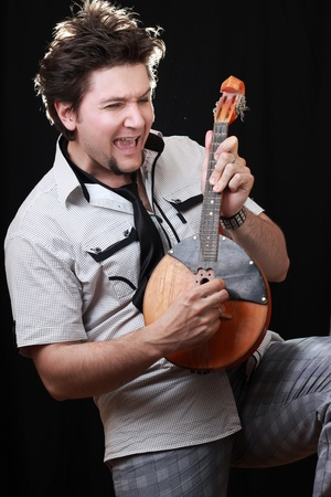 musician plays ancient instruments on a black background Stock Photo