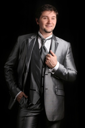 attractive man in the silver business suit on black background