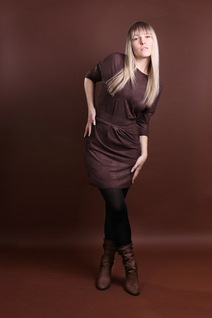young woman in full length on a brown background photo