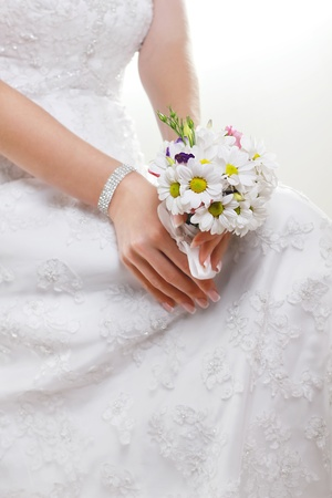 hands of bride holding a small bouquet of flowers