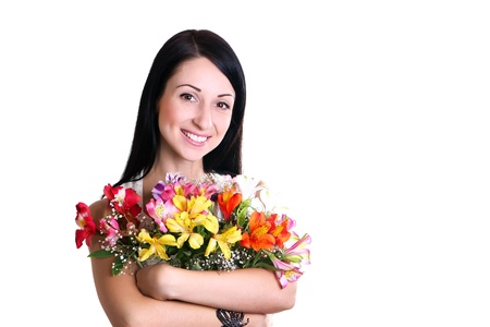 Beautiful Young Woman on a white background hugging a bouquet of colorful flowers