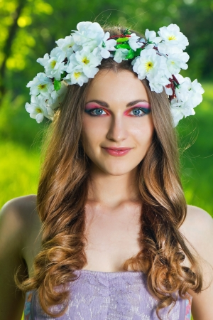 Beautiful Young Woman in a wreath with a flowers over face photo
