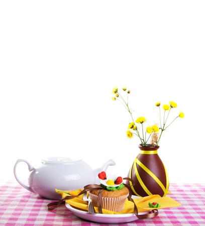 White kettle, cake and yellow flowers on a checkered tablecloth