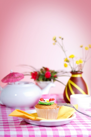 Fresh cake, White kettle, cup of tea, and yellow flowers on a checkered tablecloth
