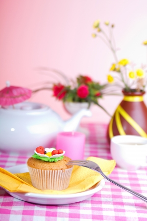 Fresh cake; White kettle; cup of tea; and yellow flowers on a checkered tablecloth photo