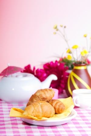 Fresh croissants; White kettle; cup of tea; and yellow flowers on a checkered tablecloth photo