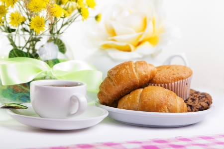 continental breakfast with croissants, cake, chocolate cookies and tea