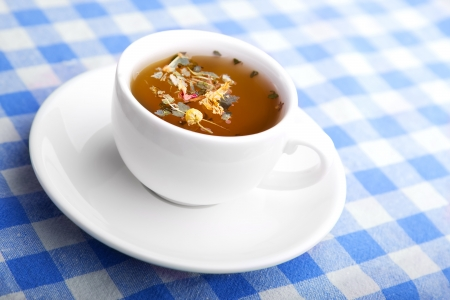 Cup of Herbal healthy Tea on a checkered tablecloth