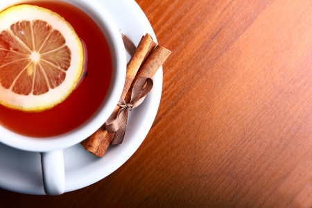 Cup of Hot Tea with Lemon and Cinnamon on wooden table Stock Photo