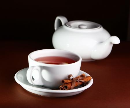 Tea with cinnamon in a dark brown interior photo