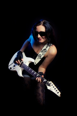beautiful young rock guitarist on a black background photo