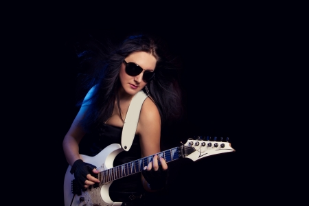 beautiful young rock Guitarist on a dark background photo
