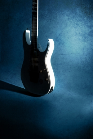musician silhouette: white silhouette of guitar on grunge blue background Stock Photo