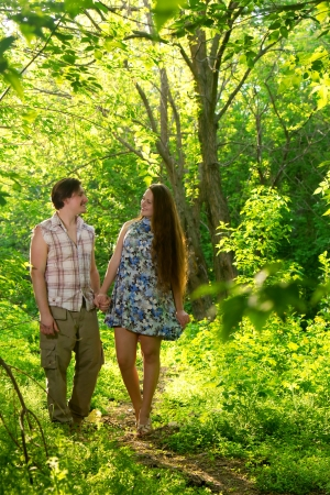 two lovers walking in the summer forest photo