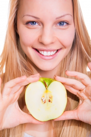 beautiful young woman shows green apple on white background photo