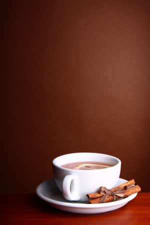 Cup of Hot Coffee with cinnamon and lemon on a wooden table