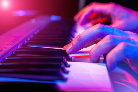 playing piano: hands of musician playing keyboard in concert with shallow depth of field Stock Photo