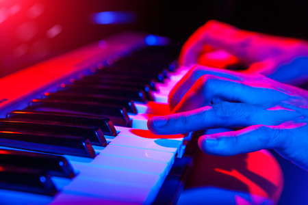 hands of musician playing keyboard in concert with shallow depth of field Stockfoto