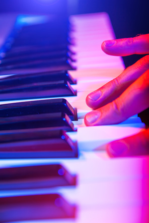hands of musician playing keyboard in concert with shallow depth of field Stock Photo