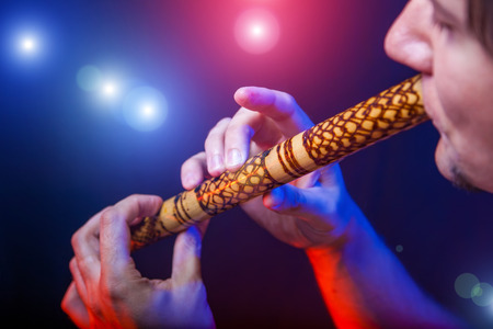 Folk musician in concert plays the melody on the Ethnic Flute Stock Photo