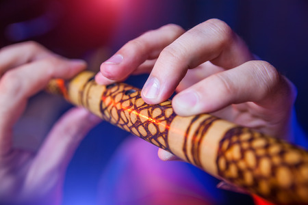 improvisation: Folk musician in concert plays the melody on the Ethnic Flute Stock Photo