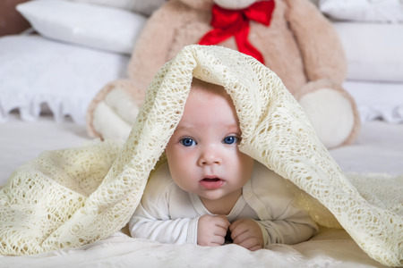baby looking out from under blanket Stock Photo