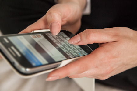 Close up of woman hands sending sms on smartphone