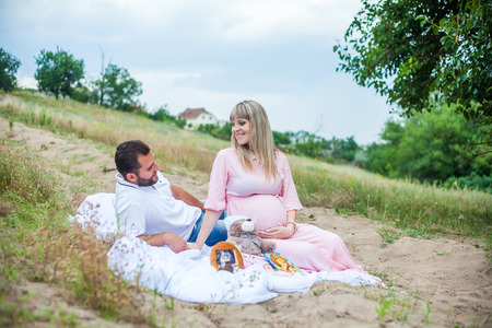 man and pregnant woman on a picnic in the countryside