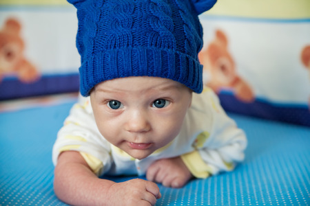 little child lying on a childrens rug in the blue cap. Small Depth of Field (DOF) Stock Photo