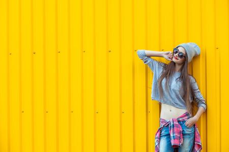cabello largo y hermoso: De moda el pelo largo hermoso Mujer joven en el sombrero y gafas de sol posando en fondo amarillo brillante