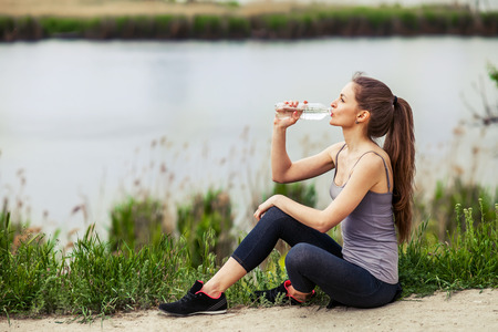 Attractive Sporty Young Woman drinking Water from a bottle after jogging or running Stock Photo