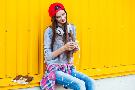 Portrait of Dreamy Young attractive Teenager in Urban background Listening to Music with from Smartphone Stock Photo