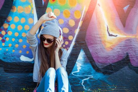 oir: Retrato de joven atractivo del adolescente en fondo urbano que escucha la m�sica con los auriculares blancos