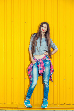 Trendy Beautiful long haired Young Woman posing on bright Yellow Background