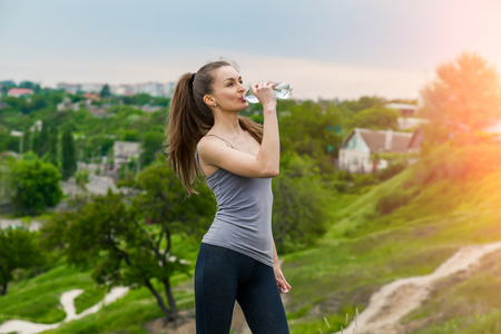 Athlete woman refreshing with Bottle of water after running workout outdoors. Woman drinking Water, Healthy active Lifestyle
