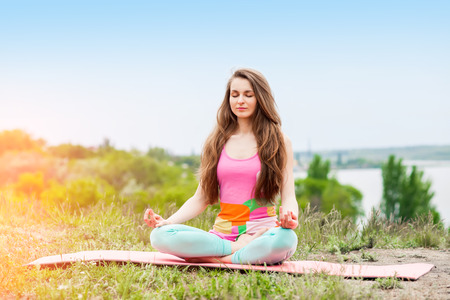 Peaceful Healthy & Fitness Young Woman Meditating on the nature with eyes closed Stock Photo