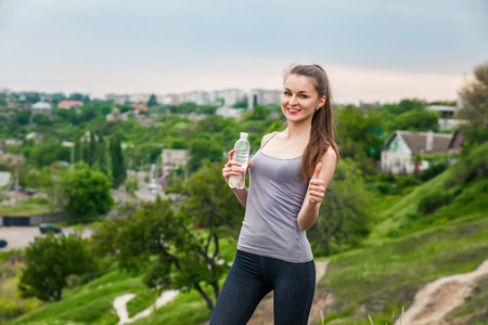 Athlete woman refreshing with Bottle of water after running workout outdoors Stock Photo