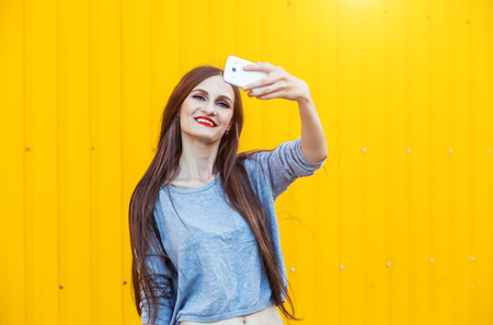 Outdoor portrait of beautiful girl taking a selfie with mobile phone in city