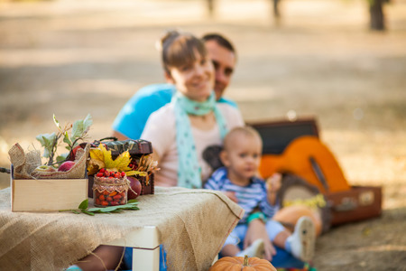 Happy family with a small child in the autumn picnic in a city park photo