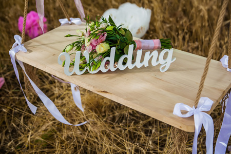 Word of wedding and bridal bouquet on the wooden swing Stock Photo