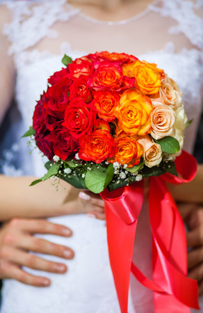 bride holding a wedding bouquet, groom gently embraces her hands