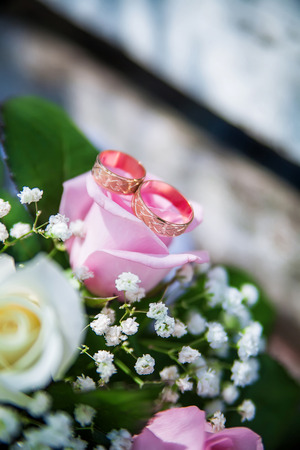wedding rings lie on the brides bouquet Stock Photo