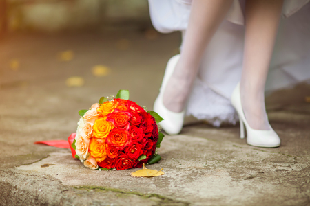 Bride in white wedding dress preparing to her wedding standing near bouquet of summer flowers showing her legs and shoes